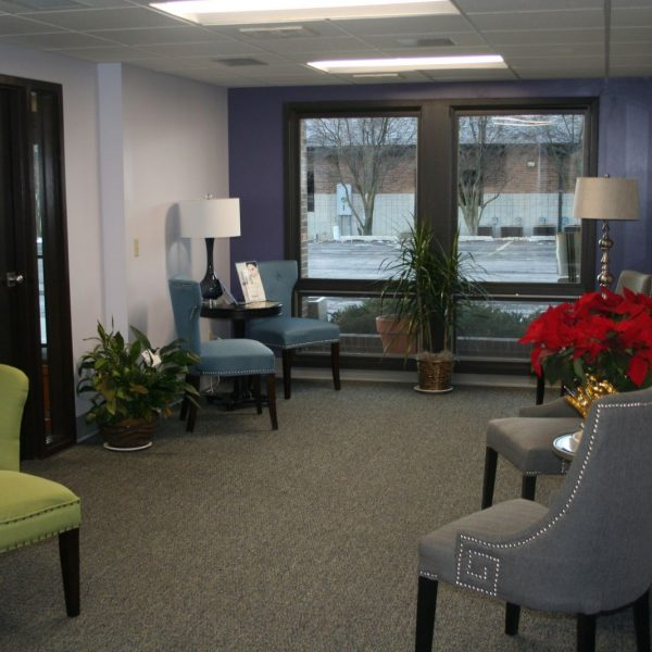 another angle of our waiting room showing grey, green, and blue chairs and a window