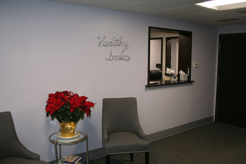 a picture of our front office greeting area with chairs and a poinsettia plant