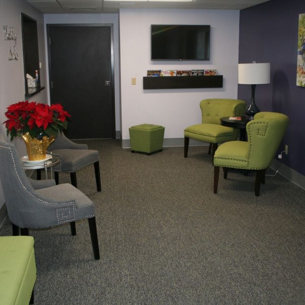 picture of our waiting room with green and grey chairs and a television