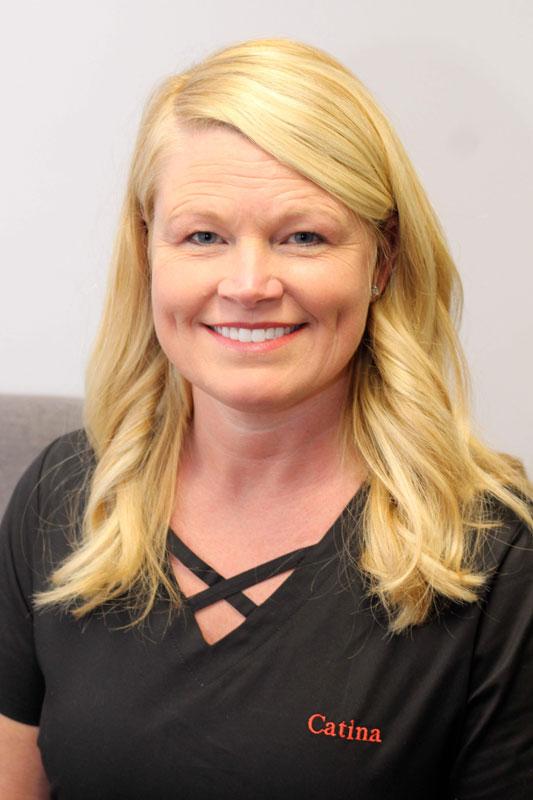 Blonde woman with long hair smiling, wearing black scrubs