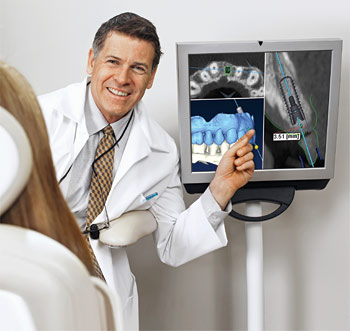 Male dentist showing a patient the results of her CBCT scan