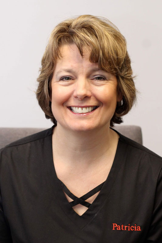 Brunette woman with short hair smiling, wearing black scrubs