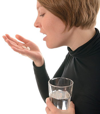 woman about to take two pills that are in her palm and holding a glass of water in her other hand
