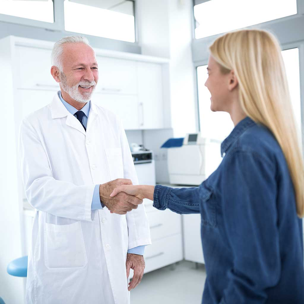 Image of an older-looking dentist, smiling and shaking a young woman's hand
