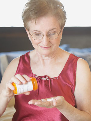 a woman pouring some pills into her hand and smiling down at them