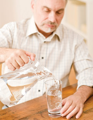 older man pouring water from pitcher
