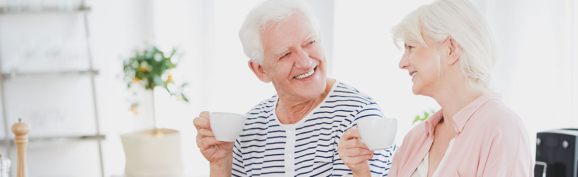 older couple sitting in their home smiling at each other and enjoying coffee in white mugs