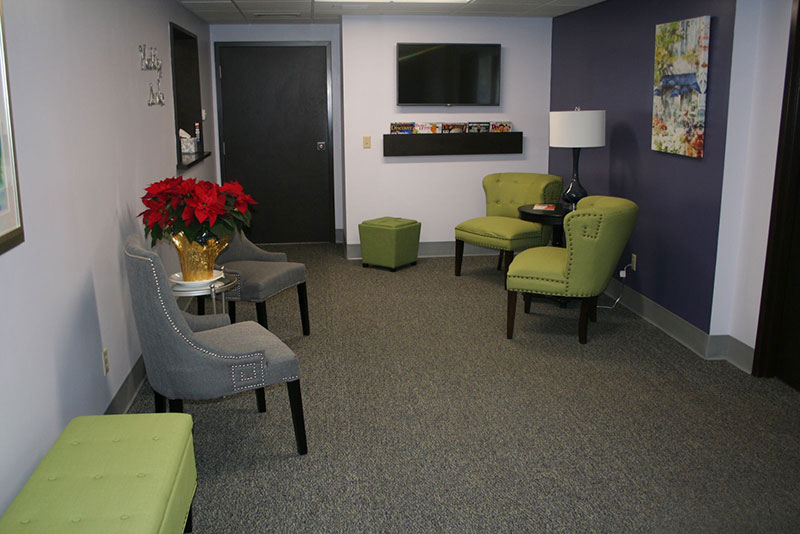 picture of our front office waiting room with green and grey chairs and a television